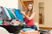 Woman sitting on couch near opened suitcase — Stock Photo