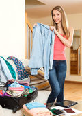 Woman standing near opened  suitcase — Stock Photo