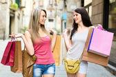 Twee lachende jonge vrouwen doen winkelen — Stockfoto