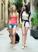 Two young travelers smiling with baggage — Stock Photo