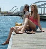 Couple of friends girls sitting near the bridge — Stock Photo