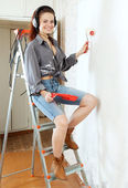 Woman in headphones with roller on stepladder — 图库照片