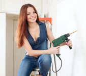 Happy girl in overalls with drill — Stock Photo