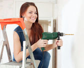 Happy woman drills hole in the wall   — Stockfoto