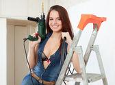 Sexy girl makes repairs at home — Stock Photo
