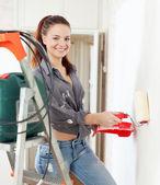 Szczęśliwa dziewczyna farby ścienne z rolką w domu — Zdjęcie stockowe