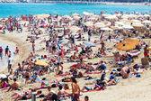 Holidaymakers sunbathing on sunny beach — Stock Photo