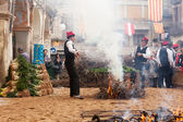 Men in traditional peasant dress cooking calsot on open fire  — Stock Photo