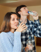 Young couple in their home drinking water — Stock Photo