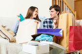 Smiling guy and girl looking at purchases — Stock Photo