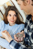 Guy giving  medicament to unwell girlfriend   — Stock Photo