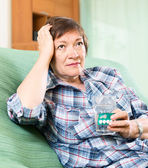 Female pensioner with pills and water — Stock Photo