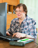使用键盘的微笑高级妇女 — 图库照片