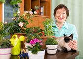 Pensioner with decorative plants — Stock Photo