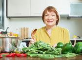 Smiling mature woman cooking okra   — Stock Photo