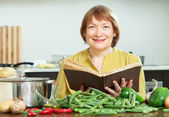 Mature woman cooking   with  cookery book in  kitchen — Stockfoto