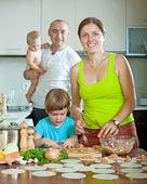 Family making ravioli with fish — Stock Photo