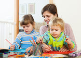 Mother and two children together with pencils — Stock Photo