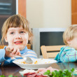 Children eating food from plates — Stock Photo