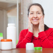 Happy mature woman puts cream on face — Stock Photo #50942593