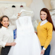 Shop assistant helps the bride in choosing dress — Photo #50942835