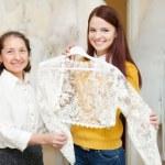 Bridesmaid with bride chooses bridal clothes — Stock Photo #50943073
