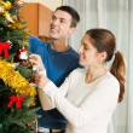 Happy couple decorating Christmas tree — Stock Photo