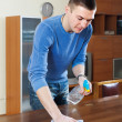 Man cleaning  table with rag and cleanser — Stock Photo #50944377