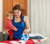 Housewife with baby ironing — 图库照片