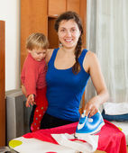 Girl with baby ironing — Stock Photo