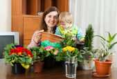 Mother with a toddler transplanting potted flowers — Stock Photo