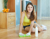 Girl rubbing wooden floor with  cleanser   — Stock Photo