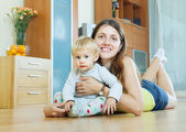 Woman with toddler on wooden floor at home — Stock Photo