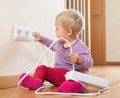 Toddler playing with extension cord — Stock Photo