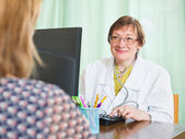 Doctor inserting information about patient — Stockfoto