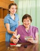 Smiling daughter asking aged mother   money  — Stock Photo