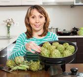 Woman cooking artichokes — Stock Photo