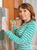 Smiling woman cleaning glass door — Foto de Stock