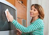 Ordinary woman cleaning TV — Stock Photo
