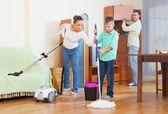 Happy family vacuuming at home — Stock Photo