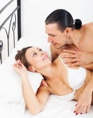 Loving awaking couple in bed  — Stock Photo