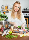 Housewife cooking  fish at kitchen table — Stock Photo