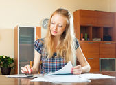 Serious long-haired woman fills in documents   — Stock Photo