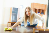 Long-haired housewife cleaning table with rag   — Stock Photo