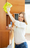 Happy housewife cleaning wooden furniture   — Stock Photo