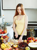 Positive long-haired woman cooking fruit salad   — Stock Photo