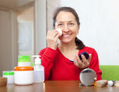 Mature woman puts facepowder on  face — Stock Photo