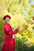 Mature woman throwing  maple leaves — Stock Photo