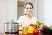 Mature woman cooking veggie lunch — Stock Photo
