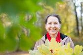 Mature woman   in autumn park — Stock Photo
